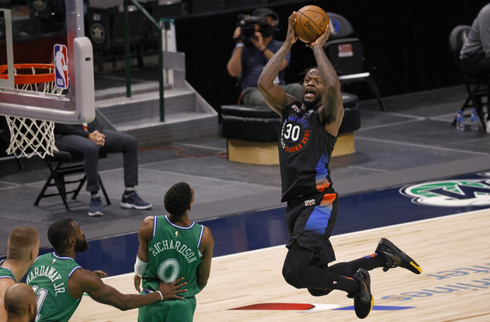 New York Knicks forward Julius Randle (30) drives inside to score as Dallas Mavericks guard Josh Richardson (0) and forward Tim Hardaway Jr. (11) watch during the second half of an NBA basketball game Friday, April 16, 2021, in Dallas. (AP Photo/Ron Jenkins)
