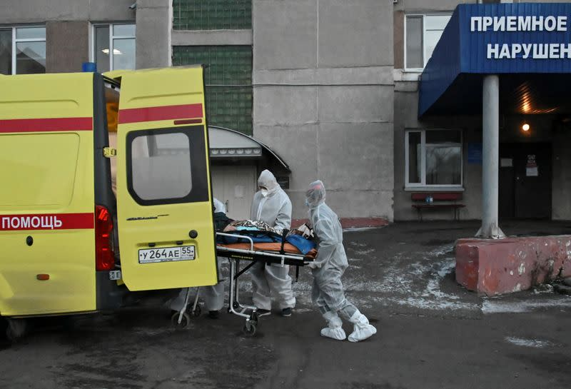 FILE PHOTO: Paramedics pull a stretcher out of an ambulance while transporting a patient amid the coronavirus disease outbreak in Omsk