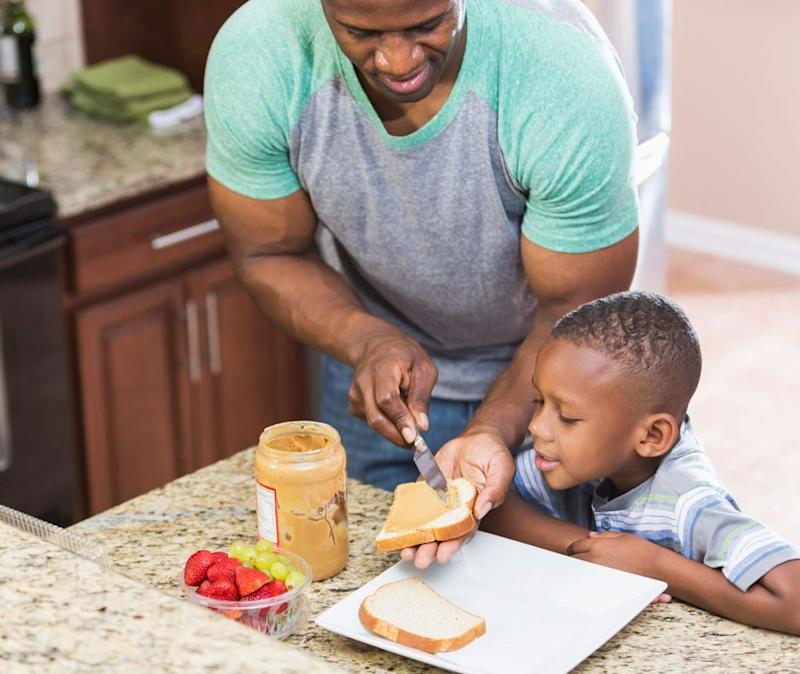 Father making his son a peanut-butter-and-jelly sandwich | Getty