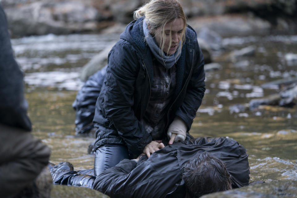 Kate Winslet in character as Mare Sheehan handcuffing a man in a river on the set of the Binge TV series Mare of Easttown