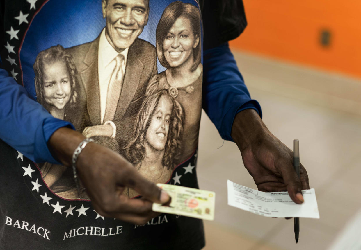 A man presents his voter identification before voting at the Rothschild Elementary School library in Columbus, Ga., on Nov. 6. (Photo: Melina Mara/Washington Post via Getty Images)