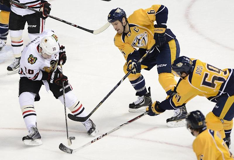 Chicago Blackhawks center Patrick Sharp (10) tries to pass the puck while being defended by Nashville Predators defensemen Shea Weber (6) and Roman Josi (59), of Switzerland, in the first period of an NHL hockey game Saturday, Nov. 16, 2013, in Nashville, Tenn. (AP Photo/Mark Zaleski)