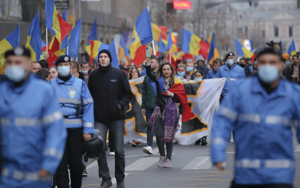 People march during a protest against the COVID-19 pandemic restrictions in Bucharest, Romania, Saturday, April 3, 2021. Thousands of anti-restriction protesters took to the streets in several cities across Romania. (AP Photo/Vadim Ghirda)