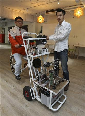 Kamm Kai-yu, a co-founder of boutique design studio Fabraft, displays a bicycle with a 3D printer installed in front, in Taipei