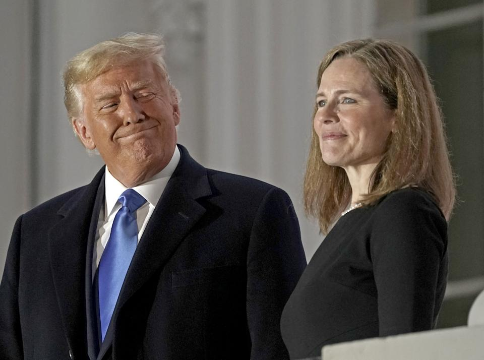 U.S. President Donald Trump, left, and Amy Coney Barrett, associate justice of the U.S. Supreme Court, stand on a balcony during a ceremony on the South Lawn of the White House in Washington, D.C., U.S., on Monday, Oct. 26, 2020. (Ken Cedeno/CNP/Bloomberg via Getty Images)