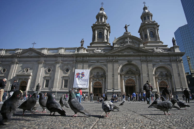"""FILE - In this May 18, 2018 file photo, pigeons are fed in front of the Santiago Cathedral, in Santiago, Chile. Pope Francis' high-stakes sex abuse prevention summit is meant to call attention to the crisis as a global problem that requires a global response. Francis discovered first-hand just how pervasive clerical sex abuse is — and how effectively it has been covered up by the Catholic hierarchy — when in January 2018 he branded as """"calumny"""" accusations of cover-up against a Chilean bishop he had strongly defended. (AP Photo/Luis Hidalgo, file)"""