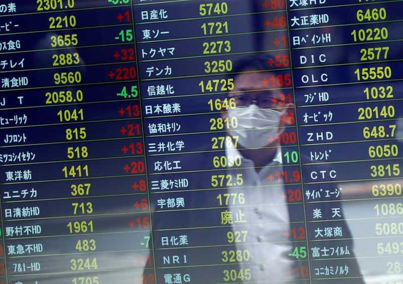 A man wearing a protective face mask is reflected on a stock quotation board at a brokerage, amid the coronavirus disease (COVID-19) outbreak, in Tokyo