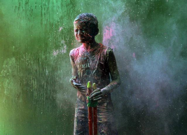 A boy reacts as other boys throw coloured powder at him during Holi celebrations in the southern Indian city of Chennai March 16, 2014. Holi, also known as the Festival of Colours, heralds the beginning of spring and is celebrated all over India. REUTERS/Babu (INDIA - Tags: SOCIETY)