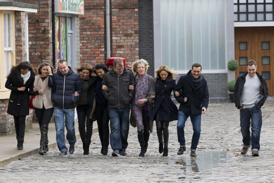 Members of the cast walk along the new set of long running British soap opera Coronation Street now based on a 7.7-acre site at Trafford Wharf in Salford Quays, Manchester, England, Friday, Nov. 29, 2013. The original set based in the central Manchester was opened by the Queen in 1982 and is only three-quarters of real size. Another new road, known as Mawdsley Street, which was until now only seen as a backdrop has also been added to the set. (AP Photo/Jon Super)