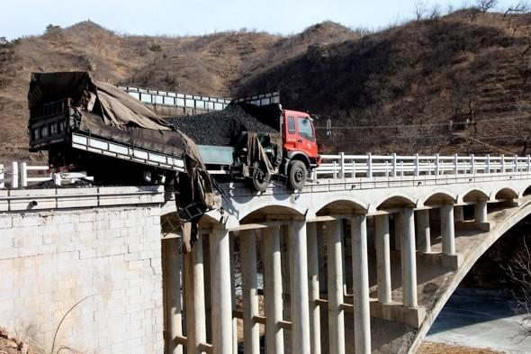 Close to the edge! Lorry crashes through bridge barrier in China