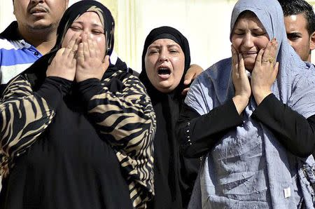 Family members of security forces killed in Sinai on Friday react as they wait for the bodies of their relatives at Almaza military airbase in Cairo