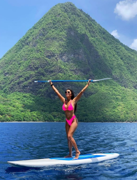Pussycat Doll Nicole Scherzinger has turned up the heat while paddle-boarding in a neon pink bikini. Photo: Instagram/nicolescherzinger.