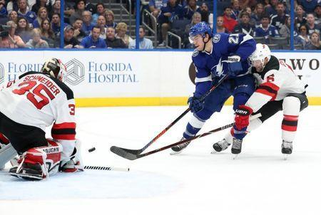 Nov 25, 2018; Tampa, FL, USA;Tampa Bay Lightning center Brayden Point (21) shoots the puck as New Jersey Devils goaltender Cory Schneider (35) defends during the first period at Amalie Arena. Mandatory Credit: Kim Klement-USA TODAY Sports