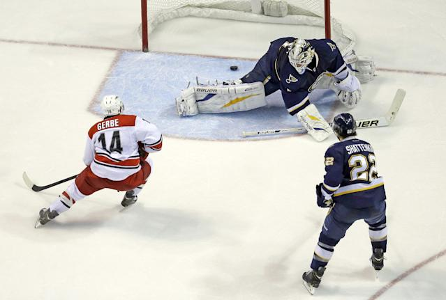 Carolina Hurricanes' Nathan Gerbe (14) scores past St. Louis Blues goalie Brian Elliott and Kevin Shattenkirk (22) during the second period of an NHL hockey game Saturday, Nov. 16, 2013, in St. Louis. (AP Photo/Jeff Roberson)