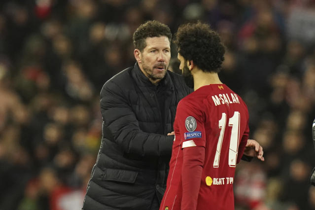 Atletico Madrid's head coach Diego Simone, left, greets Liverpool's Mohamed Salah at the end of the second leg, round of 16, Champions League soccer match between Liverpool and Atletico Madrid at Anfield stadium in Liverpool, England, Wednesday, March 11, 2020. (AP Photo/Jon Super)