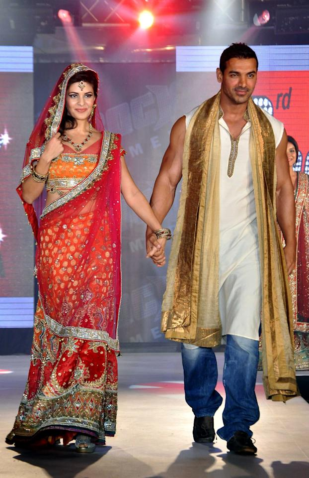 Jacqueline Fernandez and John Abraham walk the ramp wearing creations by designer Aki Narula during the promotion of their upcoming Hindi film 'Housefull 2' in Mumbai, 2012.