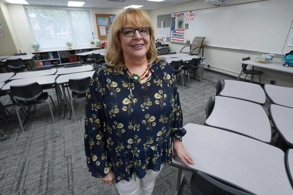 Sue Ziel, a sixth grade social studies teacher at Romeo Middle School, stands in her classroom in Romeo, Mich., Tuesday, April 27, 2021. As a veteran with experience on which she could draw, Ziel pushed through but said younger staffers were more likely to struggle with less support in a stressful time. (AP Photo/Paul Sancya)
