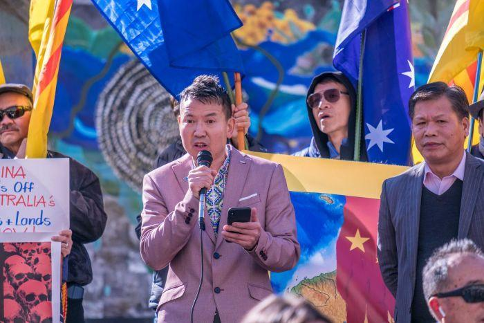 Looking up at a protest crowd, you see a man in a salmon-coloured blazer speaking into a microphone and holding a smartphone.
