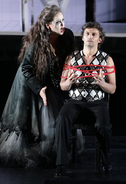 """In this picture taken Friday, June 21, 2013, Jonas Kaufmann, right, in the role of Manrico and Elena Manistina as Azucena sing during a dress rehearsal for the opera """"Il Trovatore"""" by Giuseppe Verdi in the Bavarian State Opera House in Munich, southern Germany. This wild new production by Olivier Py opened the company's annual Munich Opera Festival. It's a non-stop barrage of nightmarish images mixing styles and periods that assault the audience at lightning speed on a multi-tiered revolving set. (AP Photo/Matthias Schrader)"""