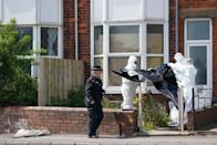 Police forensic officers work at the scene