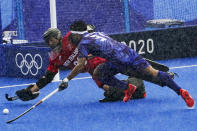 Japan's Kota Watanabe (31) leaps for a loose ball against New Zealand goalkeeper Leon Hayward in a downpour during a men's field hockey match at the 2020 Summer Olympics, Tuesday, July 27, 2021, in Tokyo, Japan. (AP Photo/John Minchillo)