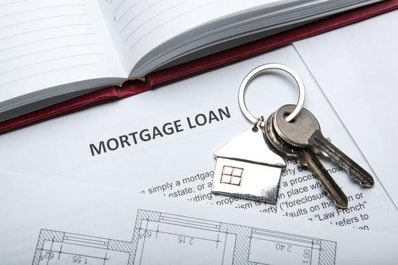 Set of house keys on top of a document headlined mortgage loan.