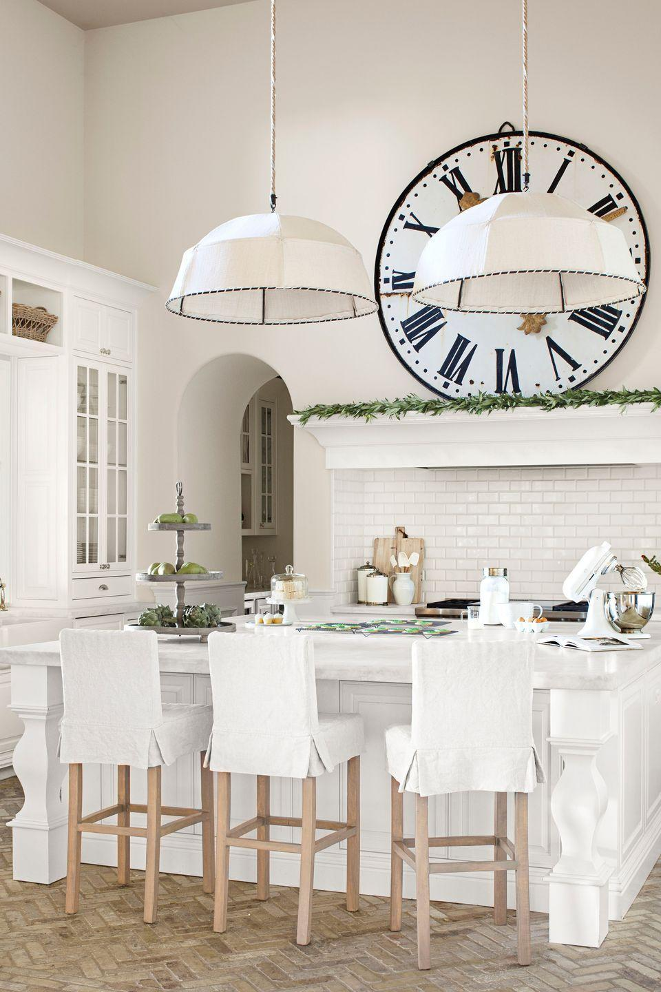 """<p>In this <a href=""""https://www.countryliving.com/home-design/house-tours/g1401/arizona-christmas-decorating-ideas/"""" rel=""""nofollow noopener"""" target=""""_blank"""" data-ylk=""""slk:Arizona home"""" class=""""link rapid-noclick-resp"""">Arizona home</a> decorated with tons of New England charm, linen-covered pendant lamps bring the kitchen's 17-foot ceilings down to a cozy scale. The owner bought the giant train-station clock on 1stdibs.com, then had the timepiece mounted to look as if it's casually propped above her Wolf range. White marble tops the custom cabinets and island. The walls are painted Exclusive Ivory and the trim Cottage White, both by Dunn-Edwards. </p>"""