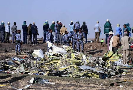 FILE PHOTO: Ethiopian Federal policemen stand at the scene of the Ethiopian Airlines Flight ET 302 plane crash, near the town of Bishoftu
