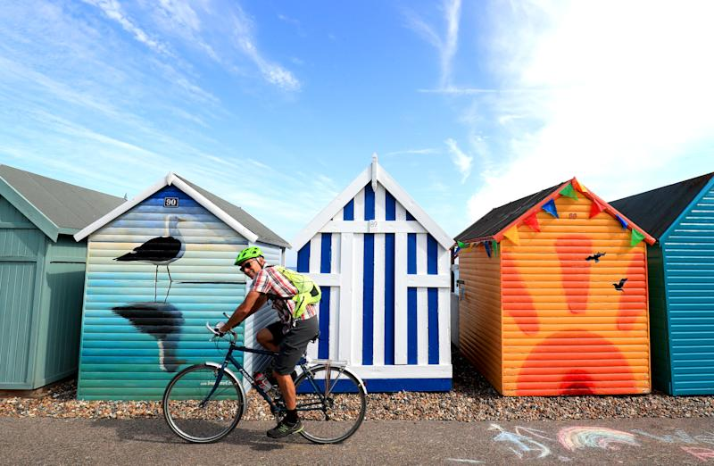 A man cycles past beach huts in Herne Bay, Kent, during the morning sunshine. (Photo by Gareth Fuller/PA Images via Getty Images)