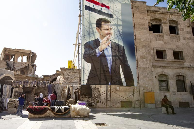 In this photo taken on Friday, Sept. 27, 2019, A huge portrait of Syrian President Bashar Assad is set in Old Market district, Aleppo, Syria. More than eight years of fighting has left many sections of Aleppo destroyed, and now authorities are pleading for international organisations to help fund restoration of the ancient city. (AP Photo/Alexander Zemlianichenko)