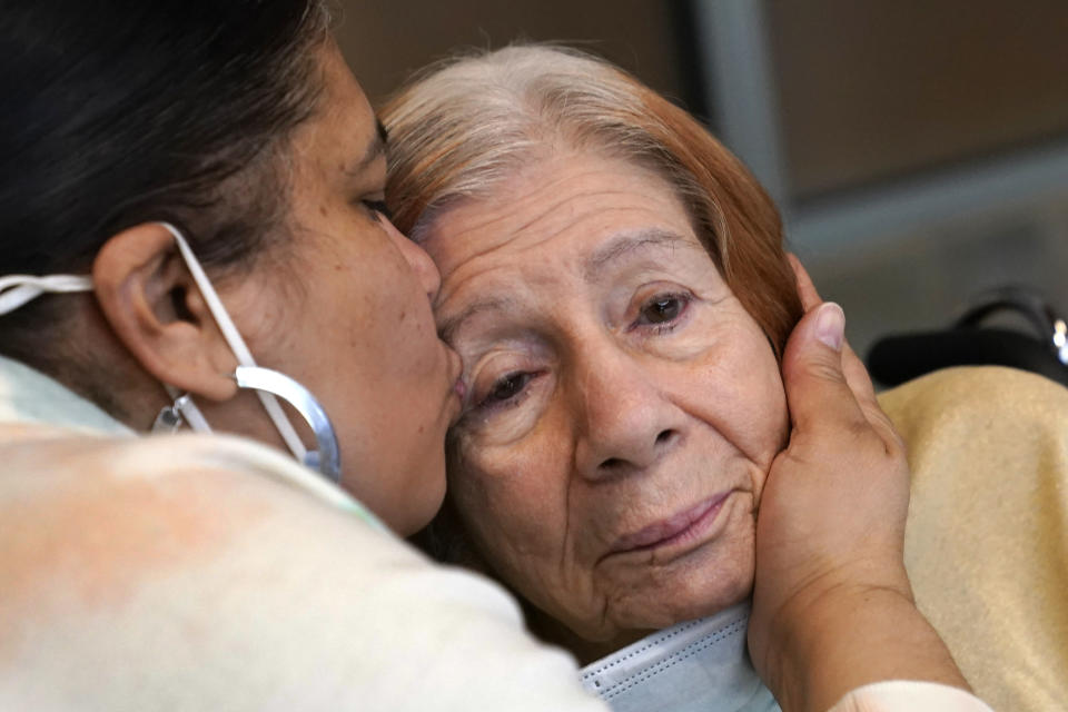 Rosa DeSoto, left, embraces her 93-year-old mother, Gloria DeSoto, who suffers from dementia, inside the Hebrew Home at Riverdale, Sunday, March 28, 2021, in the Bronx borough of New York. It was the first time in over a year that residents' families were allowed to enter the nursing home for in-person visits allowing physical contact among loved ones. Due to COVID-19 protocols, previous family visits had been made through the nursing home's windows. (AP Photo/Kathy Willens)