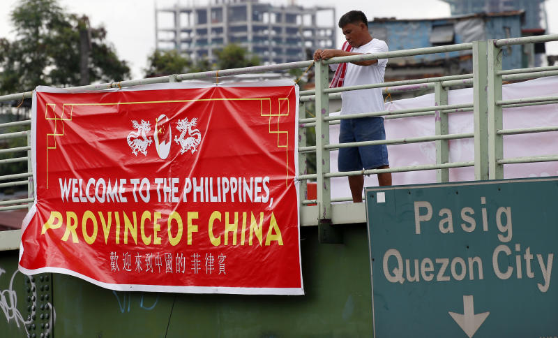 "A man tries to remove a tarpaulin banner with the words ""Welcome to the Philippines, Province of China"" that was hung from an overpass Thursday, July 12, 2018, in Manila, Philippines. Similar banners have been seen in Manila Thursday which coincided with the second anniversary of the United Nations Permanent Court of Arbitration's decision upholding the Philippines' territorial rights on some islands, shoals, and reefs in the disputed Spratlys Group of islands in the South China Sea. The decision was shelved by President Rodrigo Duterte and was never recognized by China. (AP Photo/Bullit Marquez)"