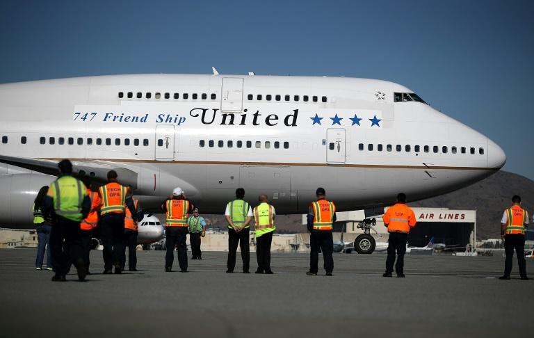 Workers look on as United Airlines Flight 747 preapres to take off from San Francisco International Airport for its final flight to Honolulu, Hawaii -- one of the last before United retires its entire Boeing 747 fleet