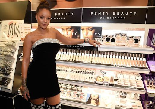 Rihanna standing next to her namesake makeup line, Fenty Beauty. (Photo: Getty Images)