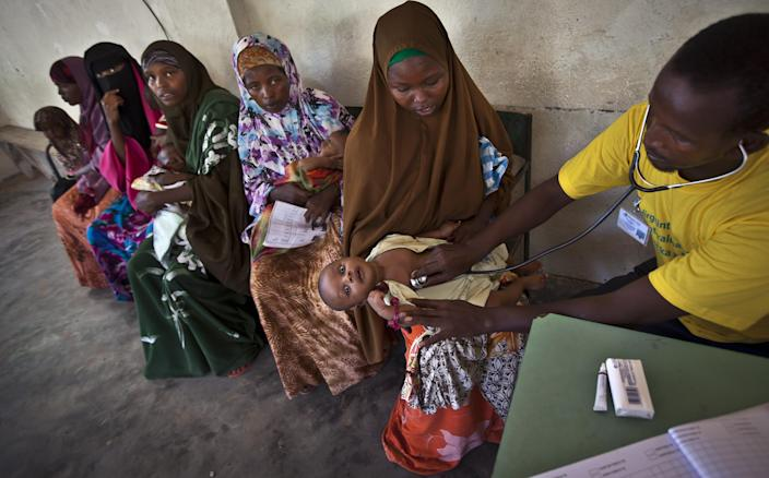 Somali mothers wait in line to have their babies examined before receiving a five-in-one vaccine against several potentially fatal childhood diseases, at the Medina Maternal Child Health center in Mogadishu, Somalia Wednesday, April 24, 2013. On the eve of the Global Vaccine Summit in Abu Dhabi and coinciding with World Immunization Week, the authorities in Somalia, which has one of the lowest immunization rates in the world, launched the new deployment of a pentavalent vaccine against diphtheria, tetanus, whooping cough, hepatitis B, and haemophilus influenzae type B the bacteria that causes meningitis and pneumonia. (AP Photo/Ben Curtis)