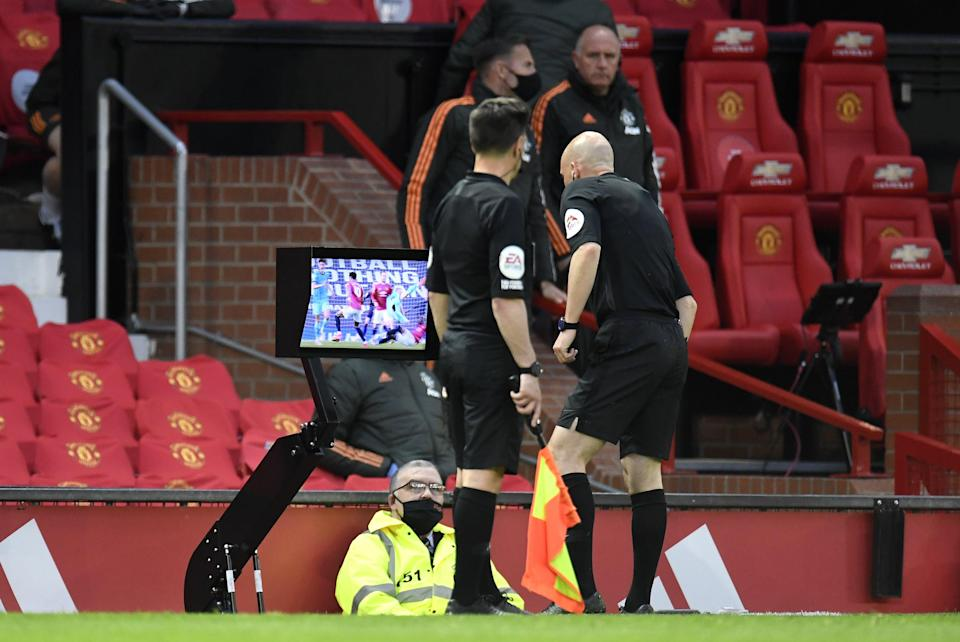 Referee Anthony Taylor consults a monitor before overturning a penalty decision in a Premier League match between Manchester United and Liverpool (Peter Powell/PA) (PA Wire)