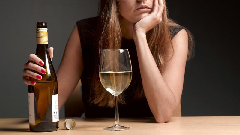 Woman hold wine bottle in front of full wine glass, with sad expression