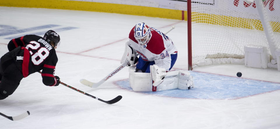 Ottawa Senators right wing Connor Brown (28) watches the puck bounce across the crease behind Montreal Canadiens goaltender Jake Allen as he falls to the ice during the first period of an NHL game Sunday, Feb. 21, 2021, in Ottawa, Ontario. (Adrian Wyld/The Canadian Press via AP)