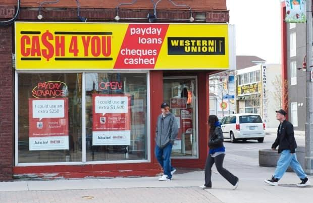 People walk pass a payday loan store in Oshawa Ont. on Saturday May 13, 2017. (Doug Ives/The Canadian Press - image credit)