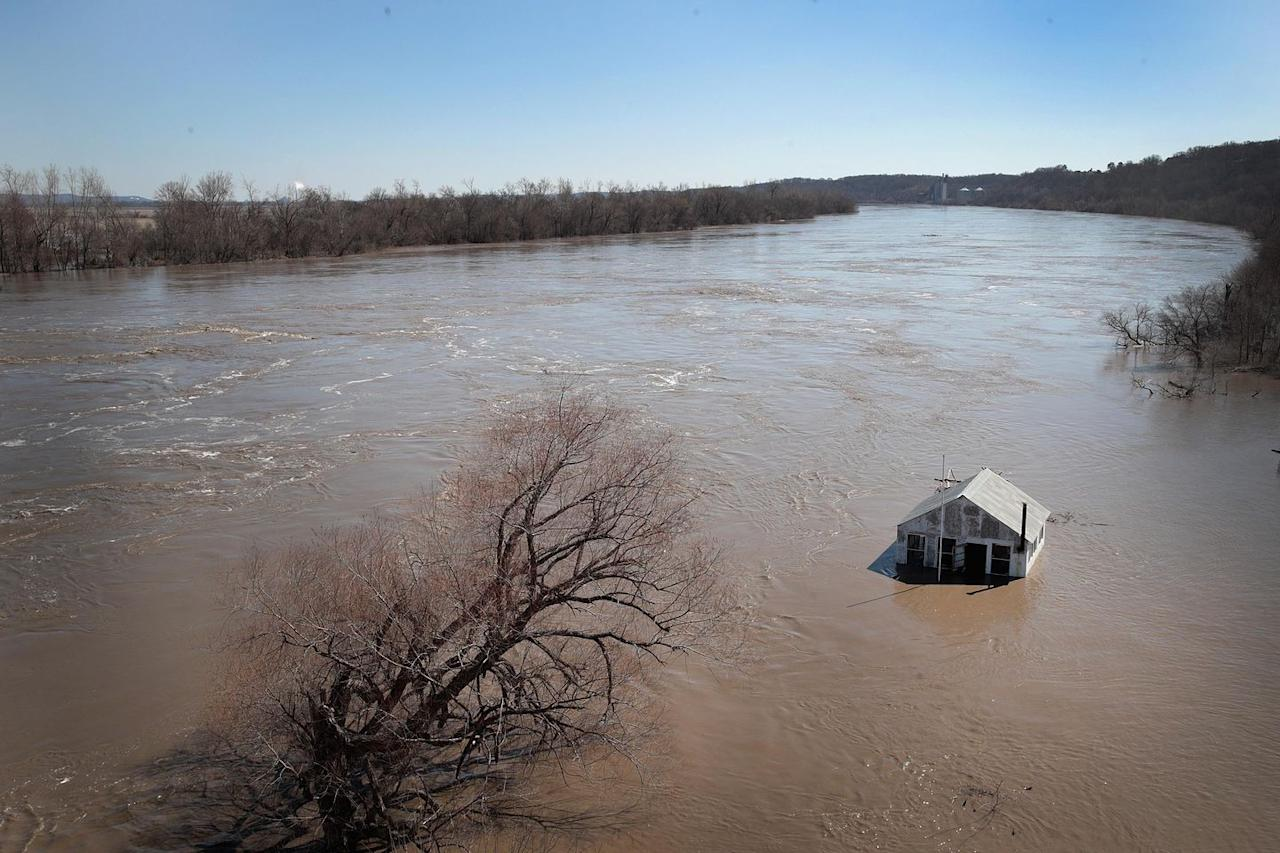 <p>Flood water began to rise in areas of the Midwest, including Nebraska, Kansas, Iowa, Illinois, and Missouri, where this aerial photo was taken on March 21, 2019 of a house besieged with water. </p>
