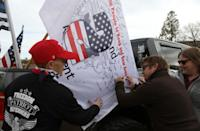 """Militia members and pro-gun rights activists sign a flag while participating in the """"Declaration of Restoration"""" rally in Washington, D.C."""