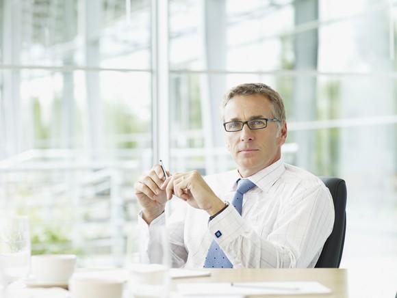 A man in an office with glass walls sits at a desk.