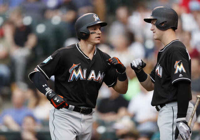 Miami Marlins' Derek Dietrich, left, is congratulated by Brian Anderson while heading back to the dugout after hitting a solo home run off Colorado Rockies starting pitcher Jon Gray in the third inning of a baseball game Friday, June 22, 2018, in Denver. (AP Photo/David Zalubowski)