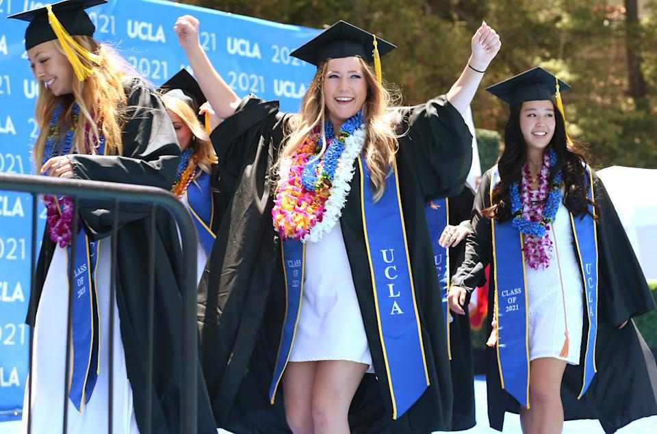 Graduating UCLA students celebrate while walking the stage for their commencement ceremony at Drake Stadium on June 11, 2021 in Westwood, California. (Photo by Mario Tama/Getty Images)