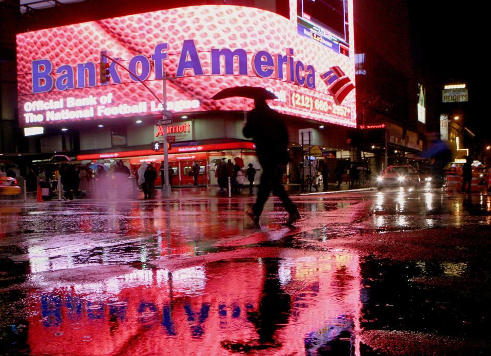 A man walks near a Bank of America branch in New York's Times Square Decemeber 11, 2008. Bank of America Corp said on Thursday it plans to eliminate 30,000 to 35,000 jobs over three years as it integrates Merrill Lynch & Co and experiences weaker business activity amid the economic recession.     REUTERS/Brendan McDermid (UNITED STATES)