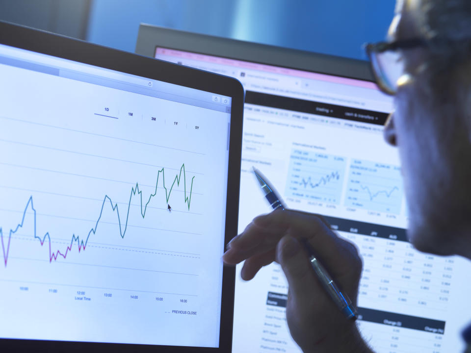 Financial services, stock analyst researching share price data of a company on the computer