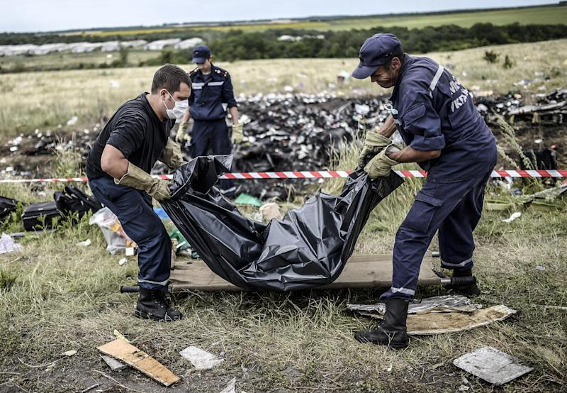 Ukrainian emergency service workers collect bodies of victims of flight MH17 at the crash site near Grabove, on July 20, 2014 (AFP Photo/Bulent Kilic)
