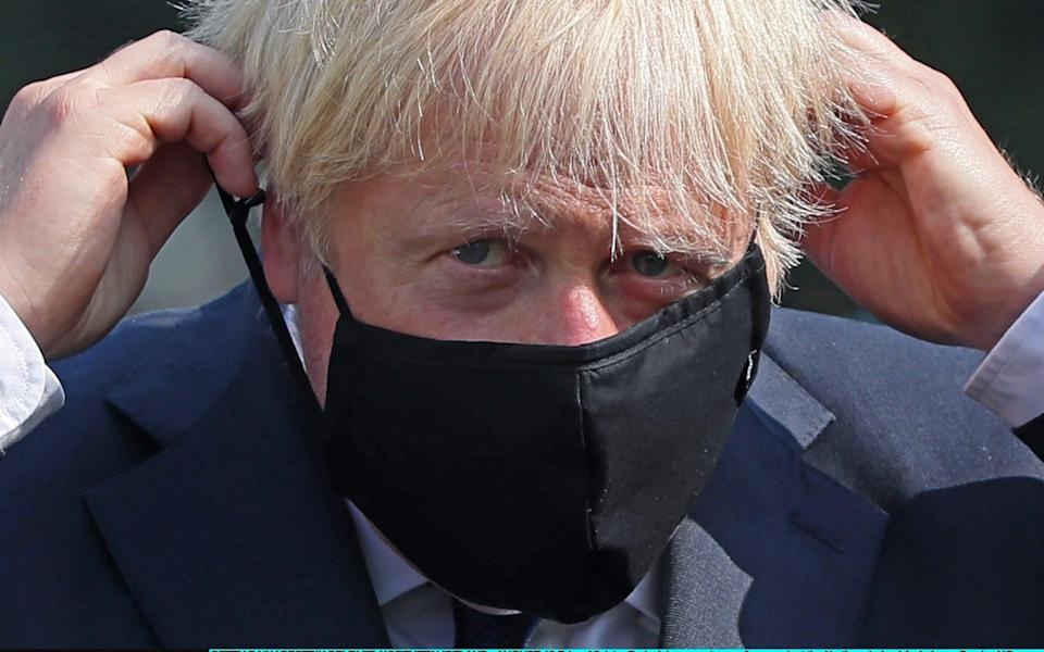 Prime Minister Boris Johnson puts on a face mask at the Northern Ireland Ambulance Service HQ during the Prime Minister's visit to Belfast on August 1 - Brian Lawless - WPA Pool