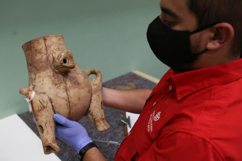 An archaeologist holds a pre-Columbian ceramic urn, which was repatriated from the Brooklyn Museum in New York, U.S., during its classification at the facilities of the Costa Rica's National Museum, in Pavas
