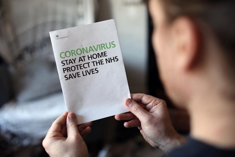 A person reads an information booklet on coronavirus sent to every UK household from the the UK Government, as the UK continues in lockdown to help curb the spread of the coronavirus. Picture date: Wednesday April 15, 2020.